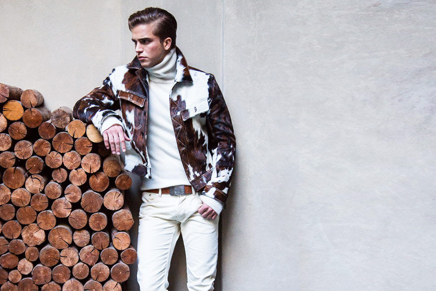 Man wearing brown-and-white spotted haircalf jacket, white turtleneck & white jean props his arm up on woodpile