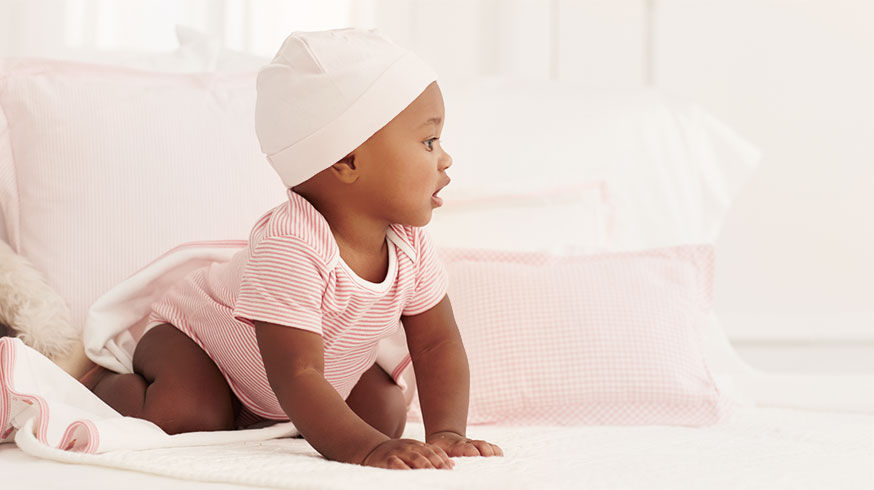 Baby starts to crawl wearing pink striped shortall and pink knit hat